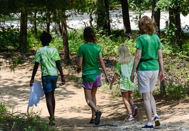 Shelia walking with three campers.